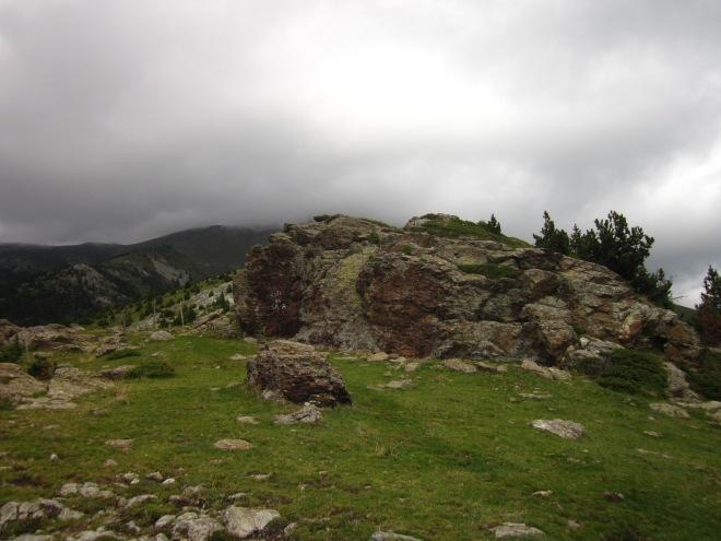 Baixem ben de pressa, amb el temps just de veure, en passar les Roques d'en Mercer, que el cim on acabem d'estar ha estat engolit pels núvols.